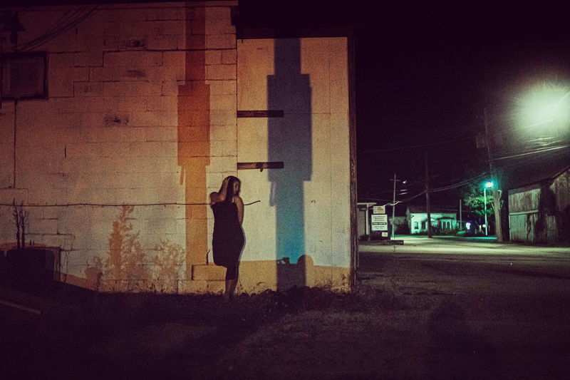 Side view of woman standing on street in city at night