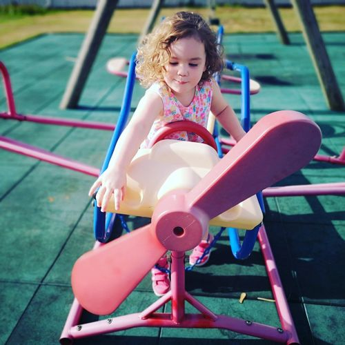 Girl standing on airplane play equipment at playground