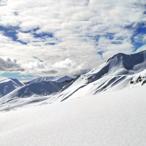 Scenic view of snow covered mountains against cloudy sky at hatcher pass