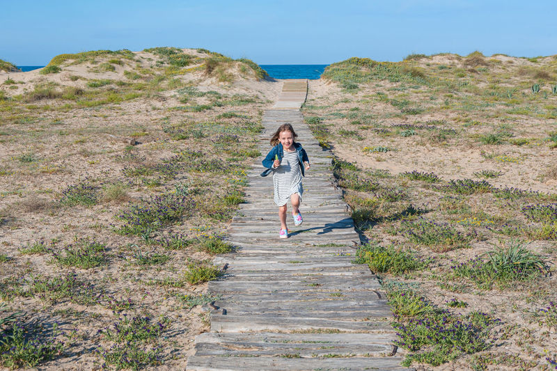 Girl running on footpath amidst grass