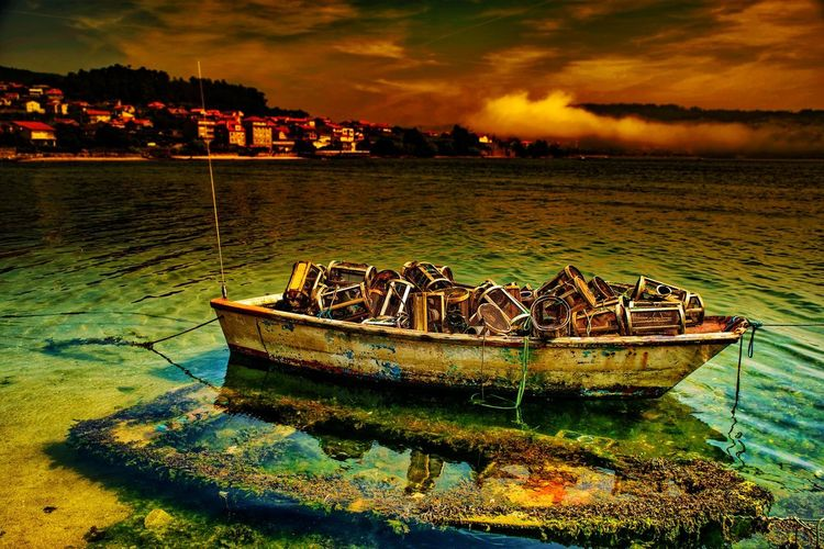 Boat moored on sea shore against sky during sunset