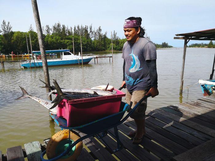 Fisherman Carrying Dead Fish In Wheelbarrow On Pier Over Lake