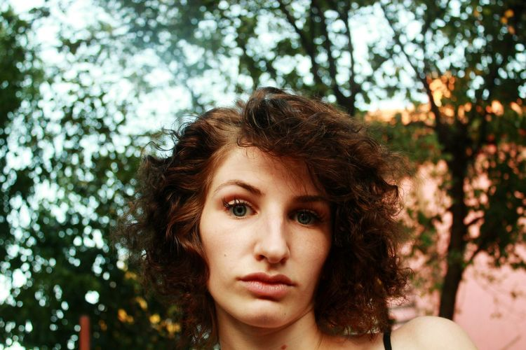 Close-up portrait of young woman with short curly hair at yard