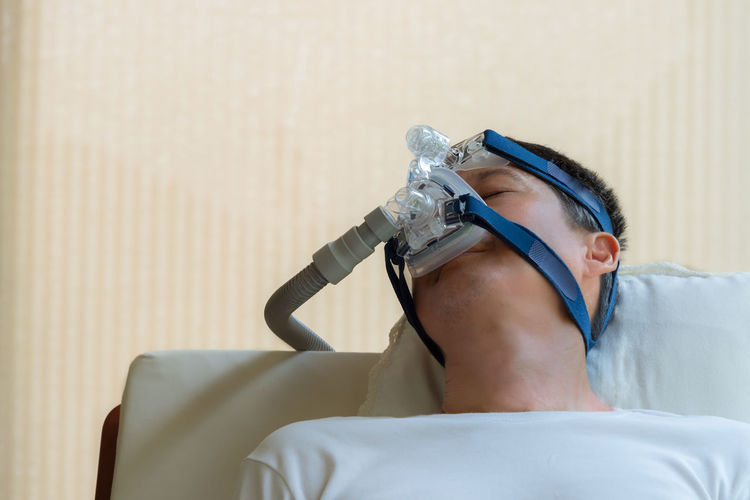 Male patient with medical oxygen equipment sleeping at hospital