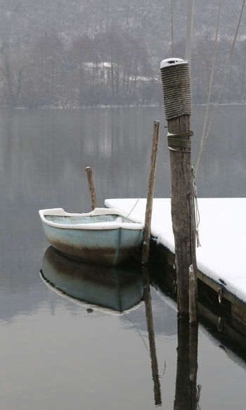 boat with snow moored on the jetty of the lake in winter Cool December Lago Di Fimon Moored Boats Pier Transportation Winter Wintertime Arcugnano Boat Cold Fimon Frozer Lake Lake View Moored Moored Boat Snow Vessel Vicenza Water