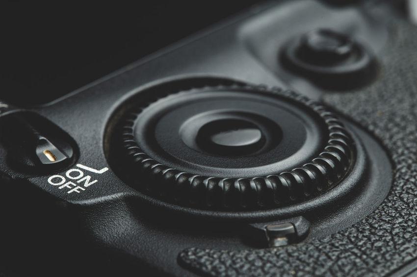 close up view of a DSLR scroll wheel in dark atmosphere Technology Close-up Photography Themes Indoors  No People Camera - Photographic Equipment Still Life Camera High Angle View Black Color Photographic Equipment Digital Camera Communication Number Shape Circle Text Selective Focus Table Equipment Wheel Control Scroll DSLR Photography