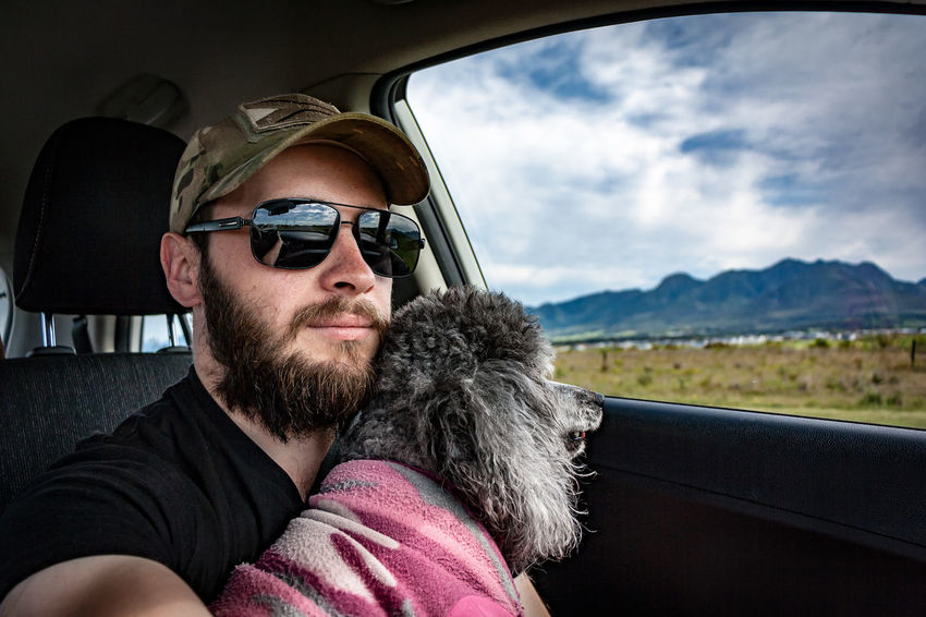 Where we go road tripping Roadtrip Dog Dogs Dogs Of EyeEm Poodles  Mananddog Mansbestfriend One Man Only Portrait Only Men Adult One Person Beard Transportation Looking At Camera Cloud - Sky Adventure Lifestyles Sky One Young Man Only An Eye For Travel