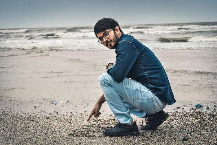 Portrait of man crouching at beach