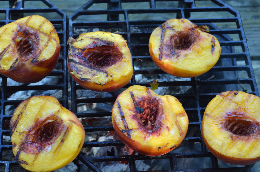 Peach halves grilling on top of a small tabletop Hibachi grill on picnic table outdoors Close-up Day Desserts Extreme Close Up Freshness Grilled Peaches Group Of Objects Halved Halves Indulgence Multi Colored No People Outdoors Peach Peach Halves Peaches Picnic Ready-to-eat Sweet Food Temptation Yellow
