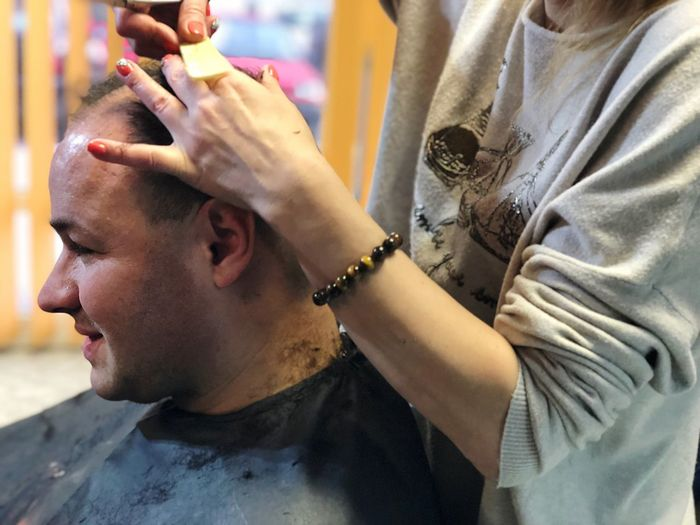 Midsection of man receiving haircut from hairdresser in salon