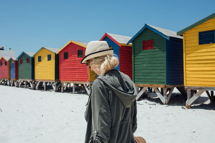 Woman walking by colorful beach huts on sunny day