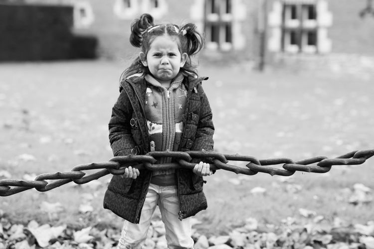 Portrait of cute girl holding chain outdoors