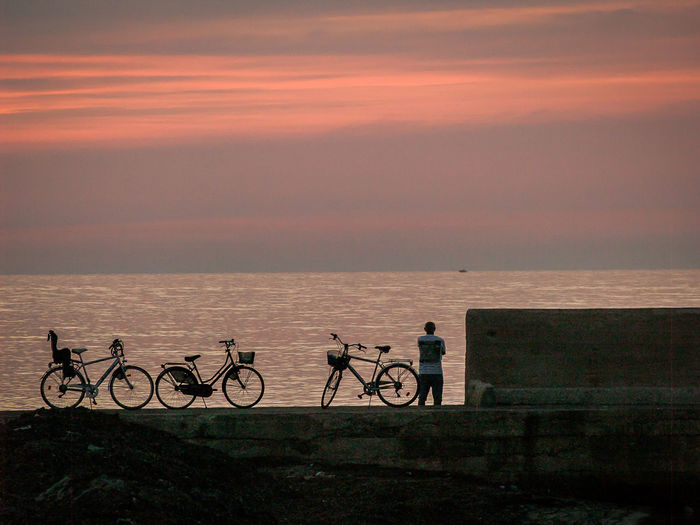 Beauty In Nature Byke Cloud - Sky Contemplation Evening Horizon Over Water Italy Leisure Activity Lifestyles Man Mode Of Transport Nature Orange Color Outdoors People Puglia Scenics Sea Sky Stationary Sunset Tranquil Scene Tranquility