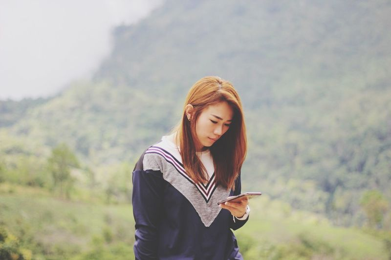 Young woman using mobile phone while standing on mountain