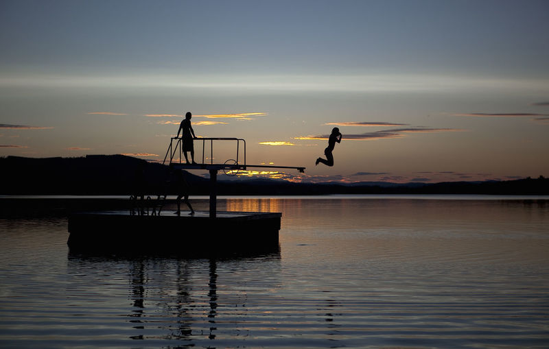 Silhouette woman jumping in lake from diving platform