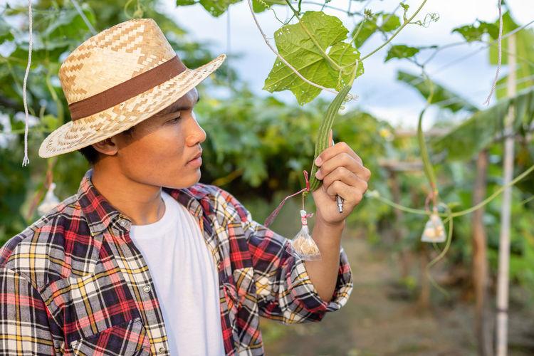 Portrait of man wearing hat holding plant