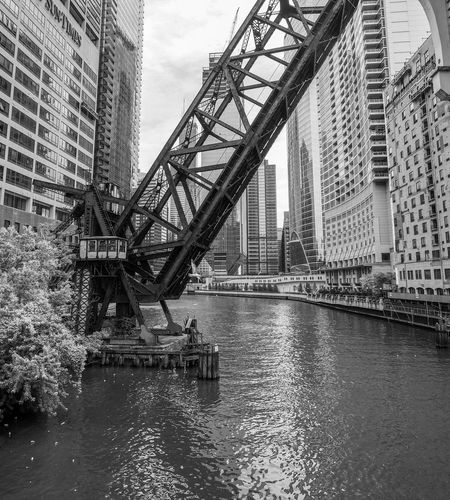 Open drawbridge over chicago river amidst modern buildings in city