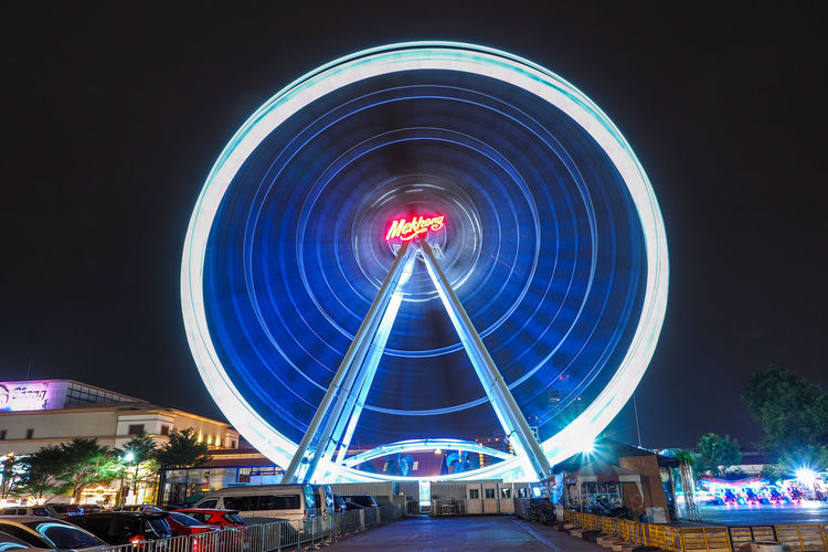 Asiatique The Riverfront Amusement Park Amusement Park Ride Architecture Arts Culture And Entertainment Asiatique Blurred Motion Building Exterior Built Structure City Fairground Ferris Wheel Glowing Illuminated Incidental People Long Exposure Motion Nature Night Nightlife Outdoors Sky Speed Spinning