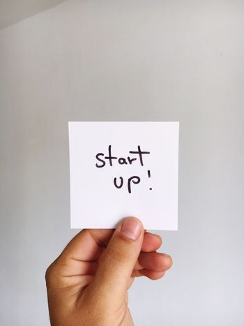 Startup Start Up Start Beginnings Beginnerphotographer Human Hand Human Body Part Text One Person Human Finger Holding Communication Personal Perspective Close-up Paper White Background Indoors  Placard Day People Begin Beginner Beginning Starter Business