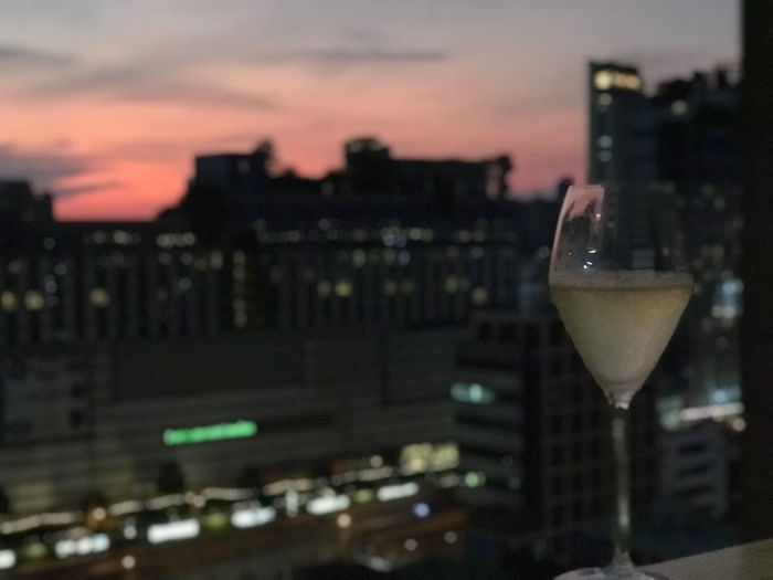 Close-up of wine glass against illuminated buildings in city