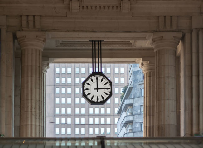 Arcade Architecture Black And White Clock Brown Building Building Background Built Structure Clock Clock Face Columns Day Facade Building Fascism Architecture Gallery Minute Hand No People Porticos Skyscarper Windows Skyscraper Station Suspended Watch Time Time To Travel Wall Watch Windows