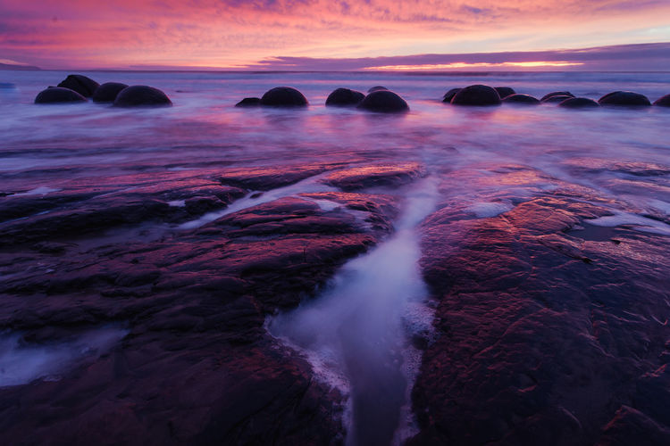 Moeraki Boulders Beauty In Nature Blurred Motion Cloud - Sky Flowing Flowing Water Idyllic Land Long Exposure Motion Nature No People Power In Nature Rock Rock - Object Scenics - Nature Sea Sky Solid Sunset Tranquil Scene Tranquility Water