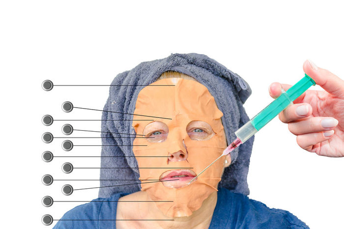 Close-up portrait of a cosmetic face mask and an injection with botulinum toxin in the female face lip zone. Botox; Injection; Plastic Surgery; Adult Gloves Holding Human Hand One Person People Studio Shot Syringe; White Background Wrinkles Of The City  Young Adult Young Women