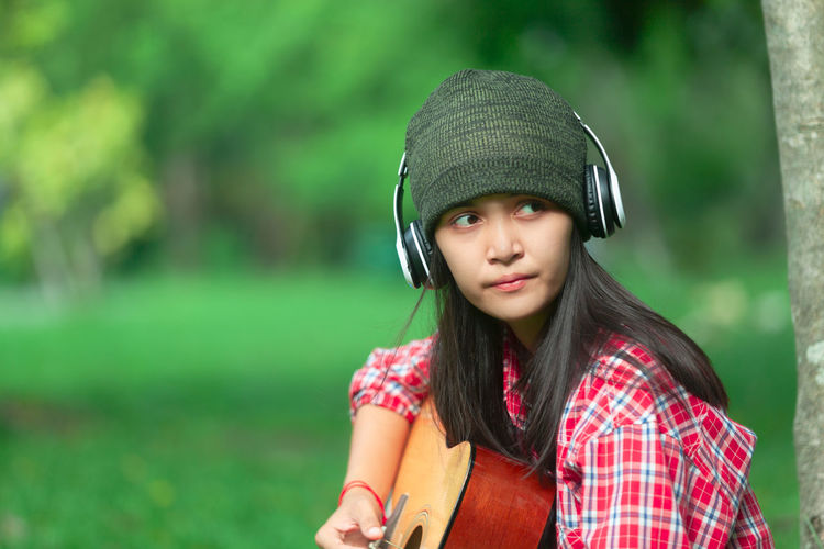 Woman Looking Away While Playing Guitar On Field
