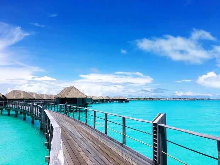 Pier By Bungalows On Lagoon Against Sky At Bora Bora Island