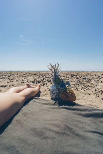 Low section of woman legs by pineapples at beach against clear blue sky