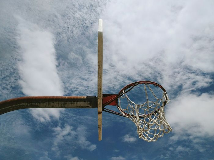 Low angle view of basketball hoop against cloudy sky