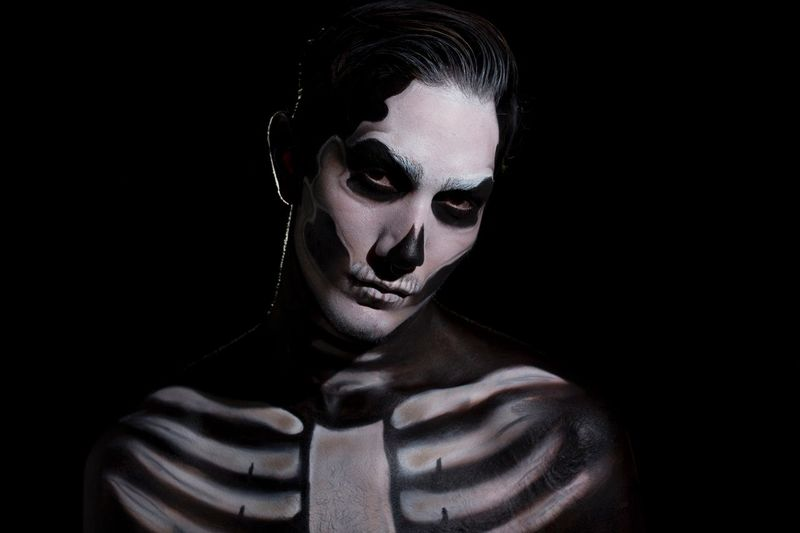 Close-up portrait of young man with halloween make-up with black background