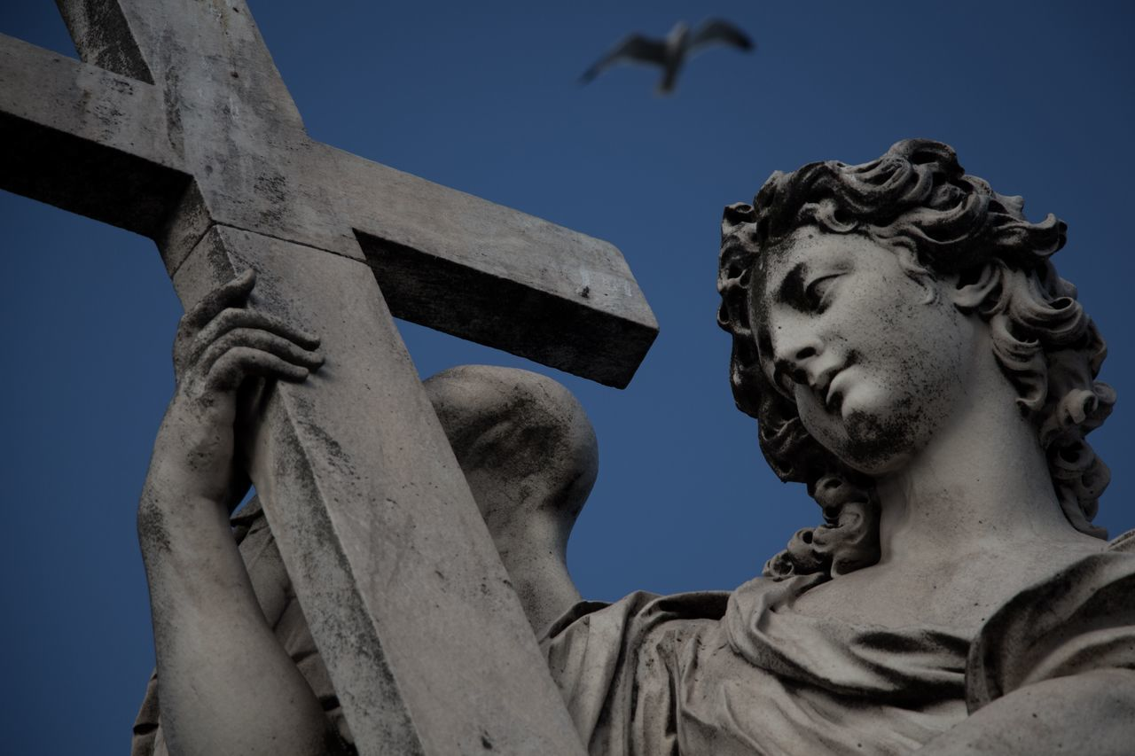 sculpture, statue, representation, art and craft, low angle view, human representation, male likeness, sky, religion, creativity, architecture, spirituality, belief, no people, day, place of worship, craft, outdoors, angel