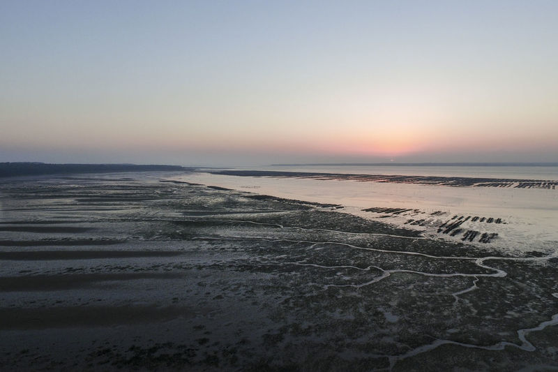 Scenic view of wet beach at sunrise