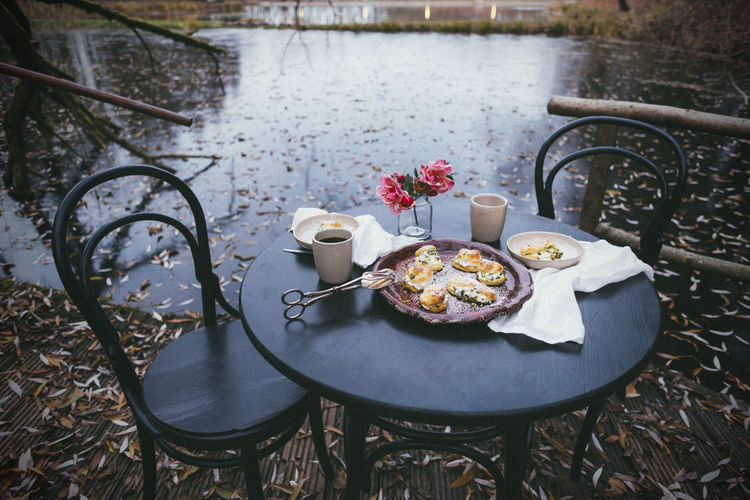 High angle view of cream puffs on table with lake in the background