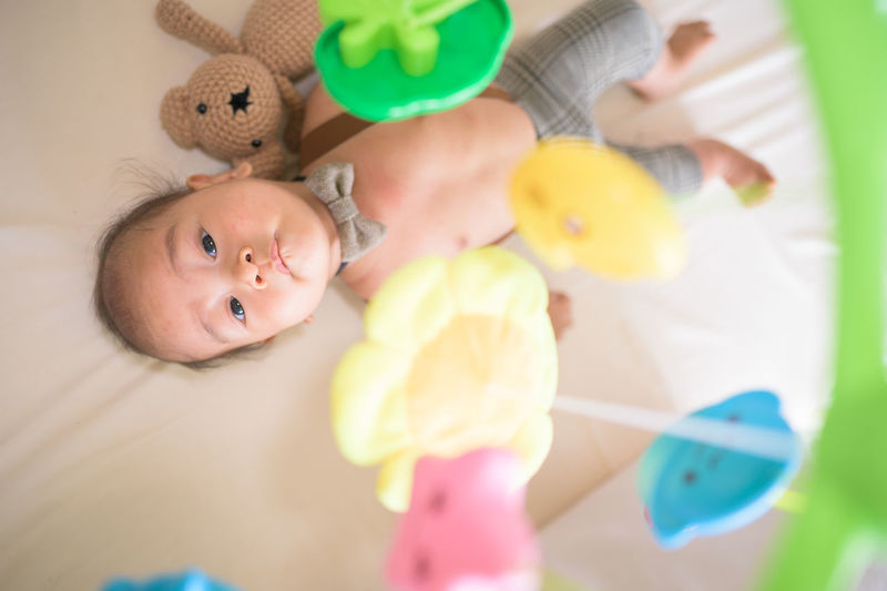 High angle view of shirtless baby boy with toys lying in crib