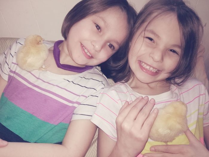 Close-Up Portrait Of Smiling Girls With Chicks