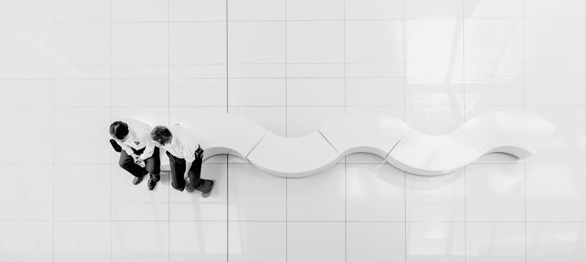 Directly Above Shot Of Men Sitting On White Curve Bench