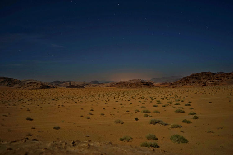 View of barren landscape with mountains at night