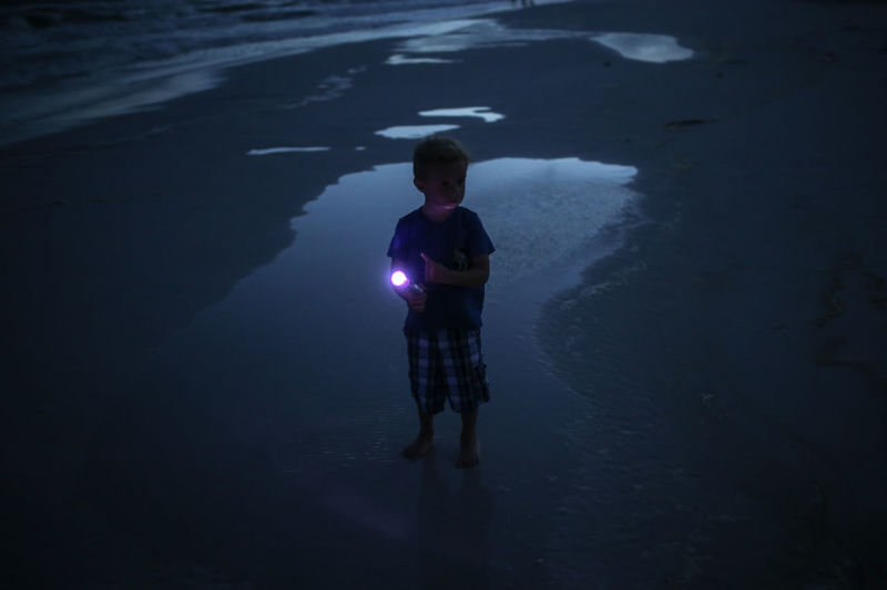 High angle view of boy holding flashlight while standing at beach