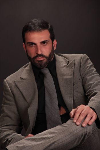 One Person Front View Looking At Camera Portrait Beard Indoors  Facial Hair Formalwear Young Adult Young Men Sitting Studio Shot Clothing Suit Three Quarter Length Well-dressed Males  Confidence  Gray Black Background Robertoblasi