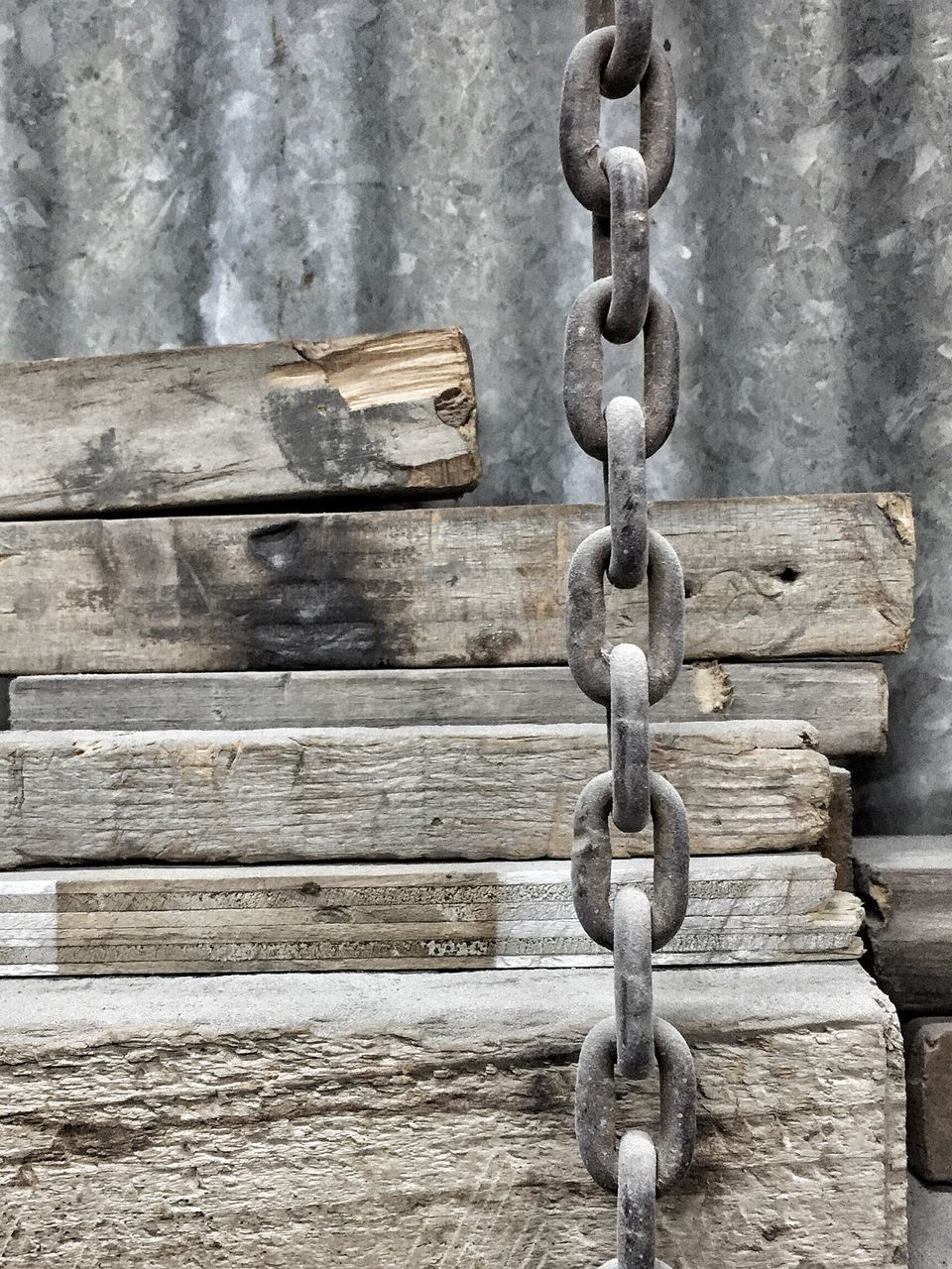 Chain Hanging By Stacked Wood Against Metallic Wall