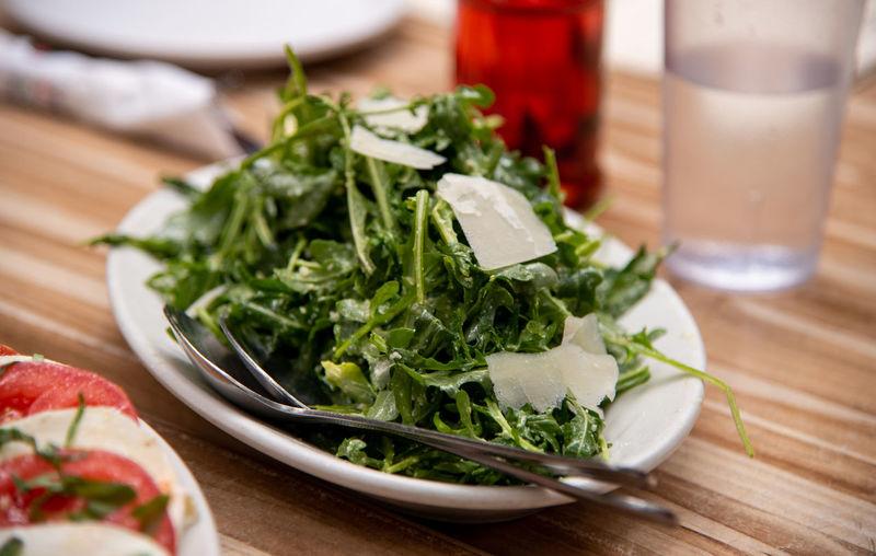 Arugula vegetable salad, Italian food Arugula Arugula Salad Salad Dish Table Vegetarian Food Drinking Glass Drink Delicious Gourmet Italian Food Cuisine Freshness Healthy Eating Menu Yummy Restaurant Eating Ready To Eat High Angle View Dinner Time Dinner Table