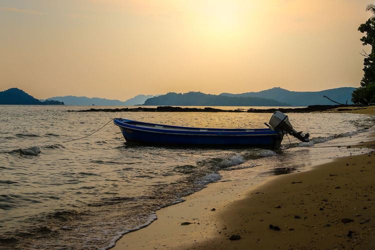 Boat moored on beach against sky during sunset