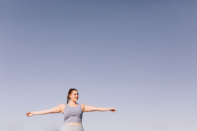 Woman with arms raised against clear sky