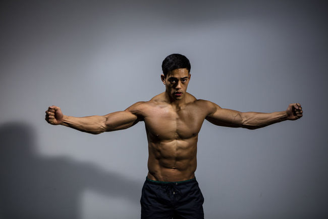 A male fitness model displaying his chiseled physique. Adult Asian  Athlete Front Facing Human Body Looking At Camera Man Shirtless Vietnamese Arms Raised Arms Spread Chiseled Clenched Fists Fitness Fitness Model Fitness Training Handsome Male Medium Shot Model Muscles Muscular Build Physique  Powerful Strong