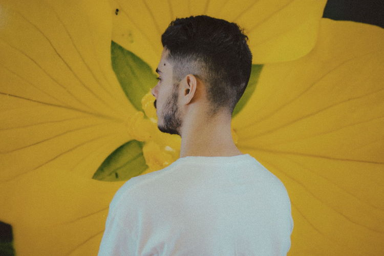 Rear view of man by yellow flower