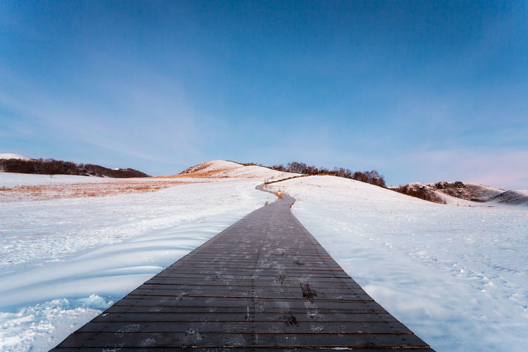 Boardwalk by snowy landscape against blue sky