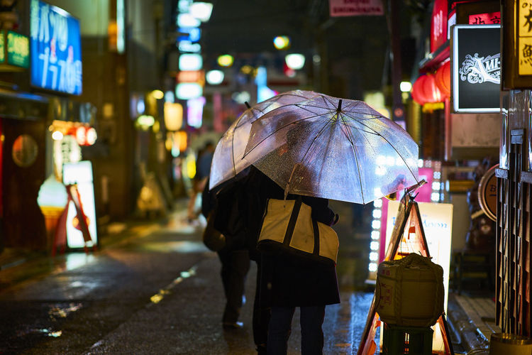 Rear View Of People With Umbrellas On Street At Night