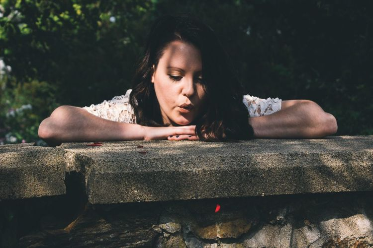 Close-up of young woman in retaining wall in park